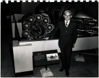 Frank Whittle with his first jet engine on display in a museum.